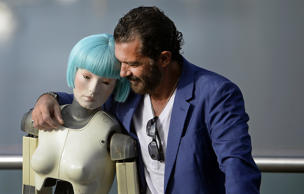 Spanish actor Antonio Banderas embraces a robot used in the film Automata during a photocall on the third day of the 62nd San Sebastian Film Festival, September 21, 2014. Banderas stars in and produced the science fiction film, which is part of the festival's official section.