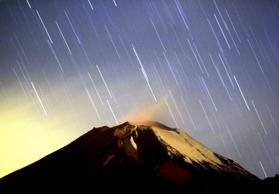 A meteor shower lights up the sky over the Mexican volcano Popocatepetl near the village San Nicolas de los Ranchos in Mexican state of Puebla in the early hours of December 14, 2004. The shower, named Geminid because it appears to originate from the constellation Gemini, lit up the sky with dozens of shooting stars per hour.