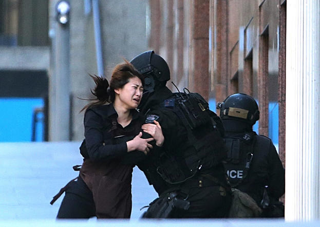 A hostage runs to armed tactical response police officers for safety after she escaped from a cafe.