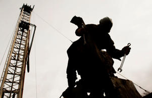 The silhouette of a rig hand is seen repairing the boom arm on a single stack dr...