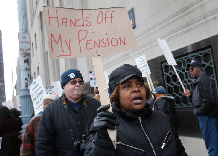Workers protest against the cutting of their pension benefits in Detroit, Michigan.