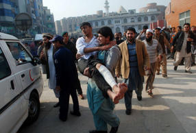 A man carries an injured student after he received treatment at a hospital in Peshawar, Pakistan, December 16, 2014.