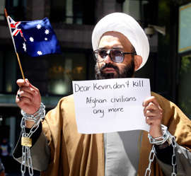 Iranian born Muslim cleric, Sheik Haron, who is named in court papers as Man Haron Monis, chained to a railing outside the Downing Centre Court in Sydney in an anti-war protest.