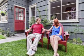 Photo of a happy young couple enjoying a summer day, sitting on lawn furniture in the back yard of their home.
