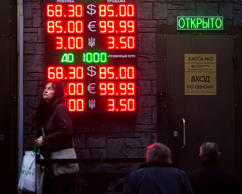 People wait to exchange currency near a sign advertising currency exchange rates at an exchange office in Moscow, Russia, Tuesday, Dec. 16, 2014. The Russian ruble came under intense selling pressure Tuesday, falling at one point by a catastrophic 20 percent to a new historic low despite a massive pre-dawn interest rate hike from Russia's Central Bank.  Russian officials were clearly rattled even though state television urged citizens not to panic.  The top two figures indicate the spread on the dollar-ruble rate and the middle two figures indicate the euro-ruble rate, with the third showing the spread on the Ukrainian hryvnia-ruble rate.