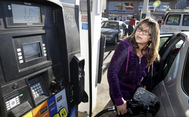 Alva Ibarra gases up at the Fuel City gas station in Dallas, Monday, Dec. 15, 2014.