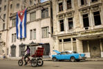 A bike-taxi and a vintage American car are seen in front of a building decorated with a large Cuban flag, on December 31, 2013, in Havana.