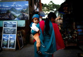 A mother carries her child as they walk in the premises of Swayambhunath Stupa in Kathmandu, Nepal, on September 9.