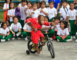 Students watch Orange, a 5-year-old orangutan, wearing a Santa Claus costume, pedalling a bicycle during a Yuletide season presentation inside a crocodile farm in Pasay city, metro Manila November 26, 2014. Filipinos are known for celebrating Christmas the longest by playing yuletide songs on local radio stations.