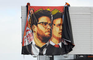 "Workers remove a poster-banner for ""The Interview"" from a billboard in Hollywood, California, December 18, 2014 a day after Sony announced it had no choice but to cancel the movie's Christmas release and pull it from theaters due to a credible threat.  Sony defended itself Thursday against a flood of criticism for canceling the movie which angered North Korea and triggered a massive cyber-attack, as the crisis took a wider diplomatic turn."