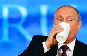 Russian President Vladimir Putin drinks during his annual end-of-year news conference in Moscow, December 18, 2014.