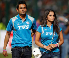 Pakistani cricketer Shoaib Malik, left, walks with his wife, Indian tennis player Sania Mirza before the start of the Indian Premier League (IPL) cricket match between Pune Warriors and Royal Challengers Bangalore in Bangalore, India, Tuesday, April 17, 2012.