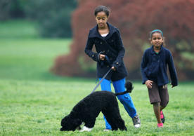 Malia Obama (L) and Sasha Obama walk their Portuguese water dog Bo in the White House.