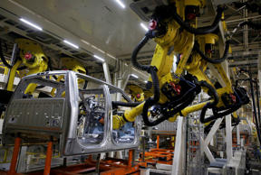 Robots assemble a 2015 Ford Motor Co. F150 truck on the production line at the company's Dearborn Truck Assembly facility in Dearborn, Mich., on Nov. 11.