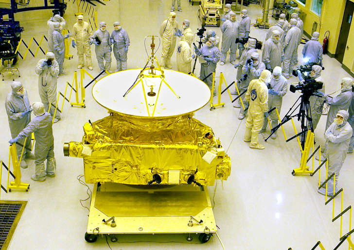 Members of the media garbed in protective unforms view NASA's New Horizons spacecraft 04 November 2005 in the Payload Hazardous Servicing Facility at Kennedy Space Center, Florida during preparations for its mid-January 2006 launch aboard an Atlas V rocket. The New Horizons will be the first mission to the planet Pluto and the Kuiper Belt, the journey taking about nine years. Pluto was discovered in 1930 at a distance of some 6.4 billion kilometers (three billion miles) from the sun in the heart of the Kuiper Belt -- a zone beyond Neptune 4.5-7.5 billion kilometers (2.8-4.6 billion miles) from the sun, which is estimated to include more than 35,000 objects of more than 100 kilomters (65 miles) in diameter: the remnants of the sun's accretion ring of matter from which all the planets were formed. AFP PHOTO/Bruce WEAVER (Photo credit should read BRUCE WEAVER/AFP/Getty Images)