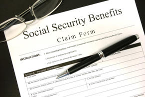 A Generic Social Security Benefits Claim Form on a clean (black) background, with a pair of reading glasses and a black pen.