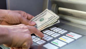 caucasian female hand picking the cash from an ATM