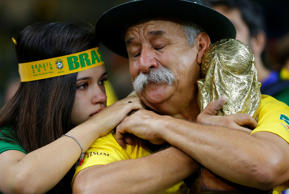 A Brazil fan holding a replica trophy is consoled after their team's 7-1 defeat to Germany in the World Cup semi-finals on July 8.