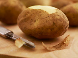 Close up of potato and peeler on cutting board.