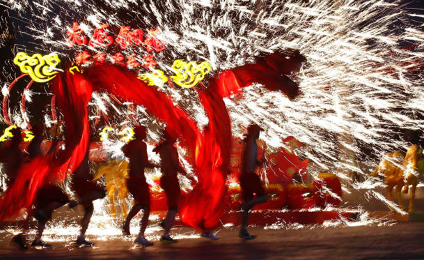 Dancers perform a fire dragon dance in the shower of molten iron spewing firework-like sparks during a folk art performance to celebrate the traditional Chinese Spring Festival on the first day of the Chinese Lunar New Year, which welcomes the Year of the Horse, at the Happy Valley amusement park in Beijing on January 31.