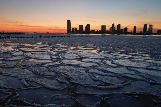 Ice floes fill the Hudson River as the New Jersey waterfront is seen during sunset on January 9 in New York City. A recent cold spell, caused by a polar vortex descending from the Arctic, caused the floes to form in the Hudson.