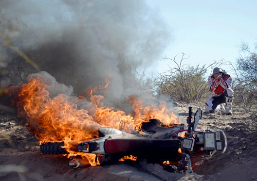 Paulo Goncalves of Portugal reacts in front of his Honda on fire during the fifth stage of the Dakar Rally 2014 from Chilecito to Tucuman on, January 9, 2014
