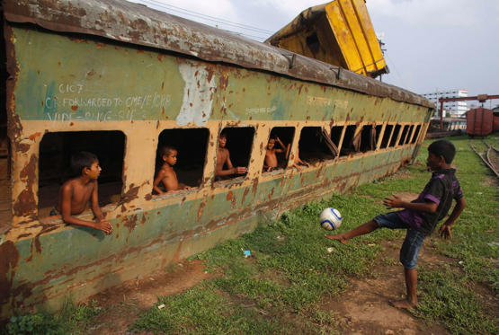 Children play football in front of an abandoned train compartment next to a railway track in Dhaka May 29, 2014. Although Bangladesh's football team is positioned 162 in the FIFA ranking, the country has millions of football fans, most supporting the national football teams of Argentina and Brazil.
