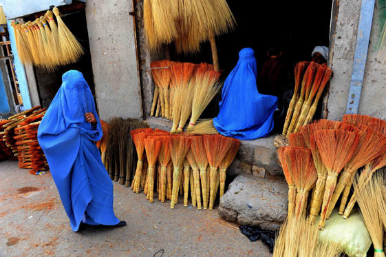 Afghan shoppers look for brooms at a roadside shop in Herat on April 9, 2014.