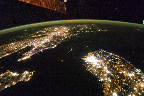 A NASA image released on February 24, 2014 shows a photo taken by the crew aboard the International Space Station (ISS) of the night view of the Korean Peninsula, and North Korea in the middle is almost completely dark compared to neighbouring South Korea (bottom right) and China (top left).