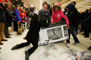 "Shoppers wrestle over a television as they compete to purchase retail items on ""Black Friday"" at an Asda superstore in Wembley, north London November 28, 2014. Britain's high streets, malls and online sites were awash with discounts on Friday as more retailers than ever embraced U.S.-style ""Black Friday"" promotions, seeking to kickstart trading in the key Christmas period. In the United States the Friday following the Thanksgiving Day holiday is called Black Friday because spending usually surges and indicates the point at which American retailers begin to turn a profit for the year, or go ""into the black""."