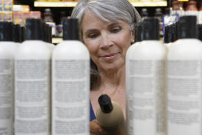 Mature woman reading shampoo label in store, close-up Getty Images (c) Noel Hend...
