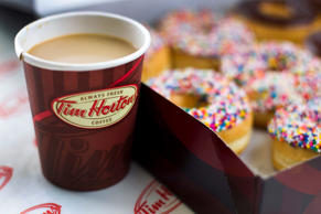 A cup of Tim Hortons Inc. coffee and doughnuts are arranged for a photograph in ...