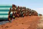 In this Feb. 1, 2012 file photo, miles of pipe ready to become part of the Keystone Pipeline are stacked in a field near Cushing, Okla.