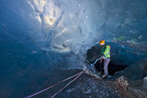 woman descending into Ice cave on the Svinafellsjokull glacier, Vatnajokull National Park, Iceland