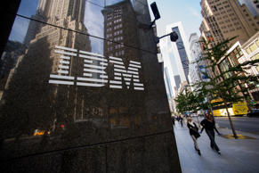 Pedestrians walk past an International Business Machines Corp. (IBM) logo that is displayed in front of the company's offices in New York, U.S., on Oct. 14, 2013.