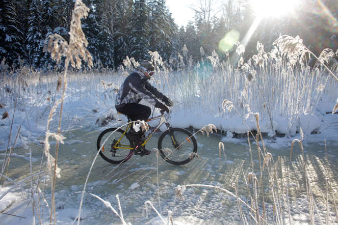 A cyclist rides his bicycle on frozen river near Ragana February 5, 2012. Many weather observation stations across Latvia registered new record-cold temperatures on Sunday according to the information from the Latvian Environment, Geology and Meteorology Center. REUTERS/Ints Kalnins (LATVIA - Tags: SOCIETY ENVIRONMENT) - RTR2XD7A