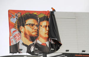 "Workers remove a poster-banner for ""The Interview"" from a billboard in Hollywood, California, December 18, 2014 a day after Sony announced was cancelling the movie's Christmas release due to a terrorist threat.  Sony defended itself Thursday against a flood of criticism for canceling the movie which angered North Korea and triggered a massive cyber-attack, as the crisis took a wider diplomatic turn."
