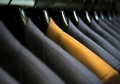 Row of hanging suits in wardrobe.