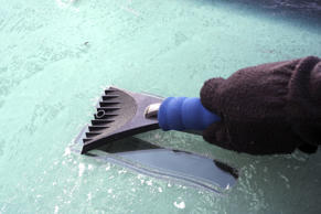 A driver wearing gloves scraping the ice off his windshield in the morning