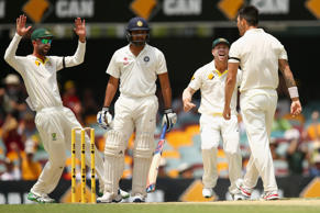 Mitchell Johnson of Australia celebrates with team mates after dismissing Rohit Sharma of India during day four of the 2nd Test match between Australia and India at The Gabba on December 20, 2014 in Brisbane, Australia.