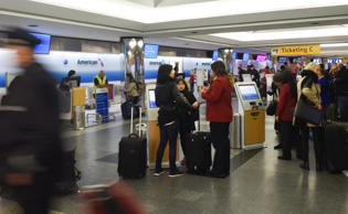 Travelers check-in to flights on November 27, 2014, at LaGuardia Airport in New York City.