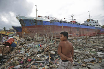 A young survivor stands beside ships that were washed ashore by Typhoon Haiyan at Tacloban city, central Philippines on Saturday, Dec. 7, 2013. Typhoon Haiyan, one of the most powerful storms on record, hit the country's eastern seaboard Nov. 8, leaving a wide swath of destruction and displacing more than 4 million people.  Aaron Favila/AP