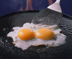 Fried eggs on frying pan.   MIXA Co. Ltd./Getty Images