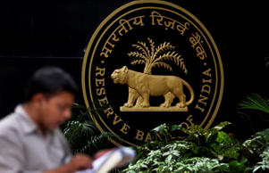 File: A media person speaks on phone next to the logo of the Reserve Bank of India (RBI) in Mumbai, India
