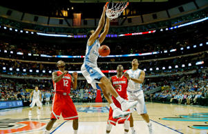 North Carolina forward Brice Johnson (11) dunks as forward Kennedy Meeks (3) and Ohio State forward Sam Thompson (12), guard Shannon Scott (3) look on during the first half of an NCAA college basketball game in CBS Sports Classic on Dec. 20, 2014, in Chicago.