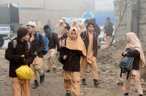 Pakistani children arrive at their school in Peshawar on December 20, 2014, after three days of mourning for the children and staff killed by Taliban militants in an attack on an army-run school.