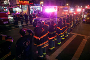 An ambulance carrying one of the two New York Police officers who were shot dead passes by a New York Fire Department honor guard along Broadway in New York City, Dec. 20, 2014. A gunman ambushed and fatally shot two New York police officers on Saturday and then killed himself, police said.