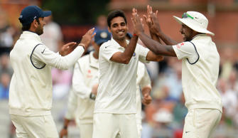 India's Bhuvneshwar Kumar (2nd R) celebrates with team-mate Varun Aaron (R) after the dismissal of England's Chris Jordan during the fourth cricket test match at the Old Trafford cricket ground, Manchester, England August 8, 2014.