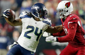 Running back Marshawn Lynch of the Seahawks pushes off cornerback Patrick Peterson of the Cardinals to break free for a 79-yard touchdown in the fourth quarter Dec. 21 in Glendale, Ariz.