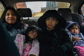From left, Rocio Morales, 8, Heidi Jocelyn Flores Morales, 4, Edwin Gordillo Morales, 10, and Mia Flores Morales, 1, ride in the back seat of the family's car en route to school but running late on Tuesday, December 9, 2014, in Akron, OH.